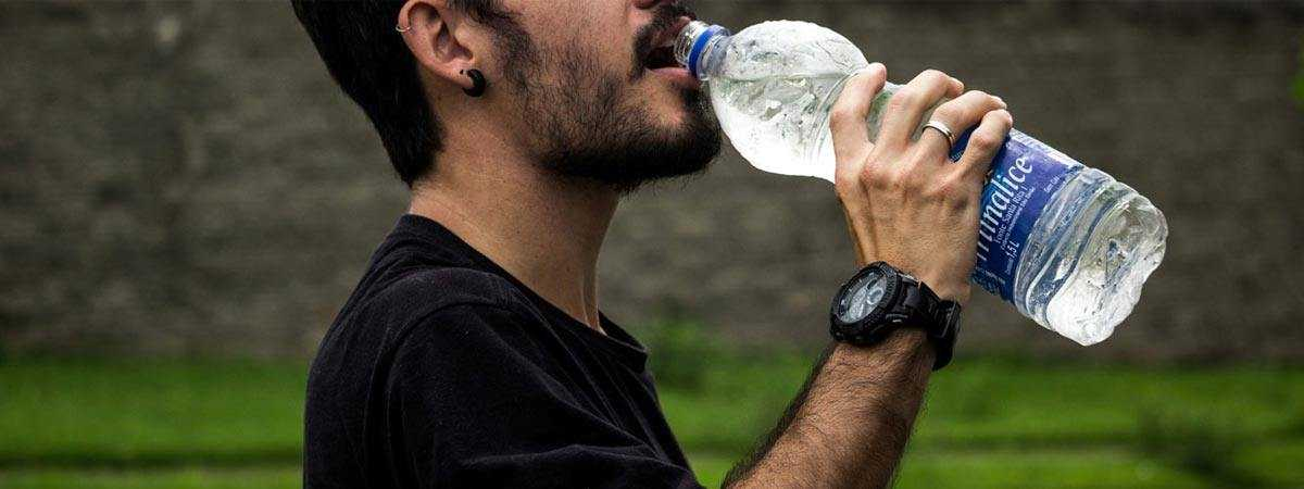man drinking from bottle of water