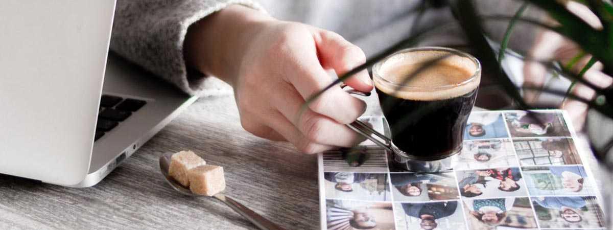 person reading a magazine holding an espresso