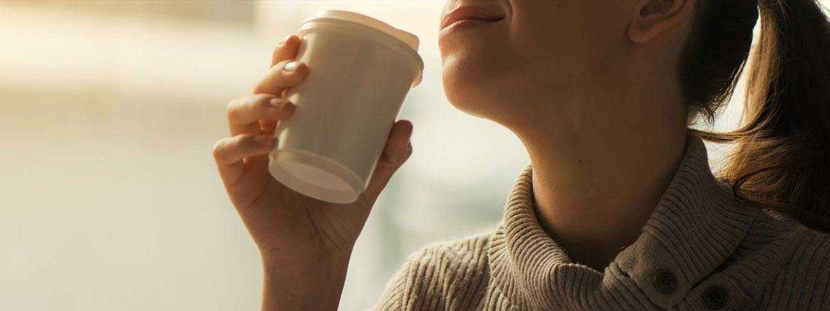 woman drinking from takeaway cup