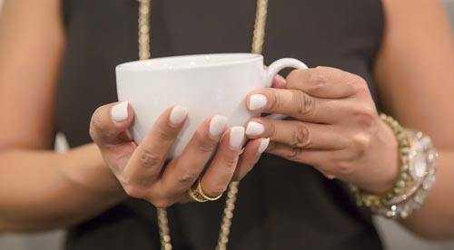 woman holding white coffee mug