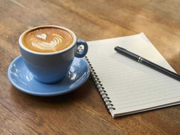 notebook next to coffee