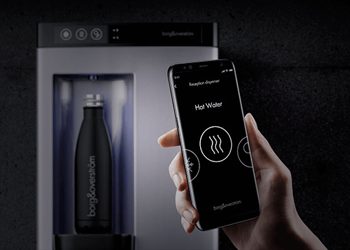 Hand holding smartphone that is displaying the Borg and Overstrom app. In the background a countertop water dispenser is filling a sports bottle