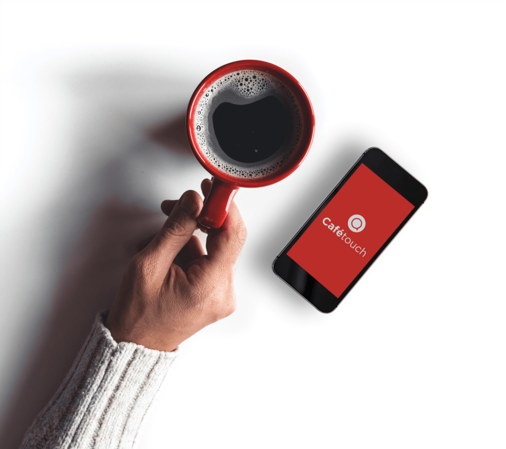 Hand holding red mug of black coffee with mobile phone to the right showing the cafetouch app