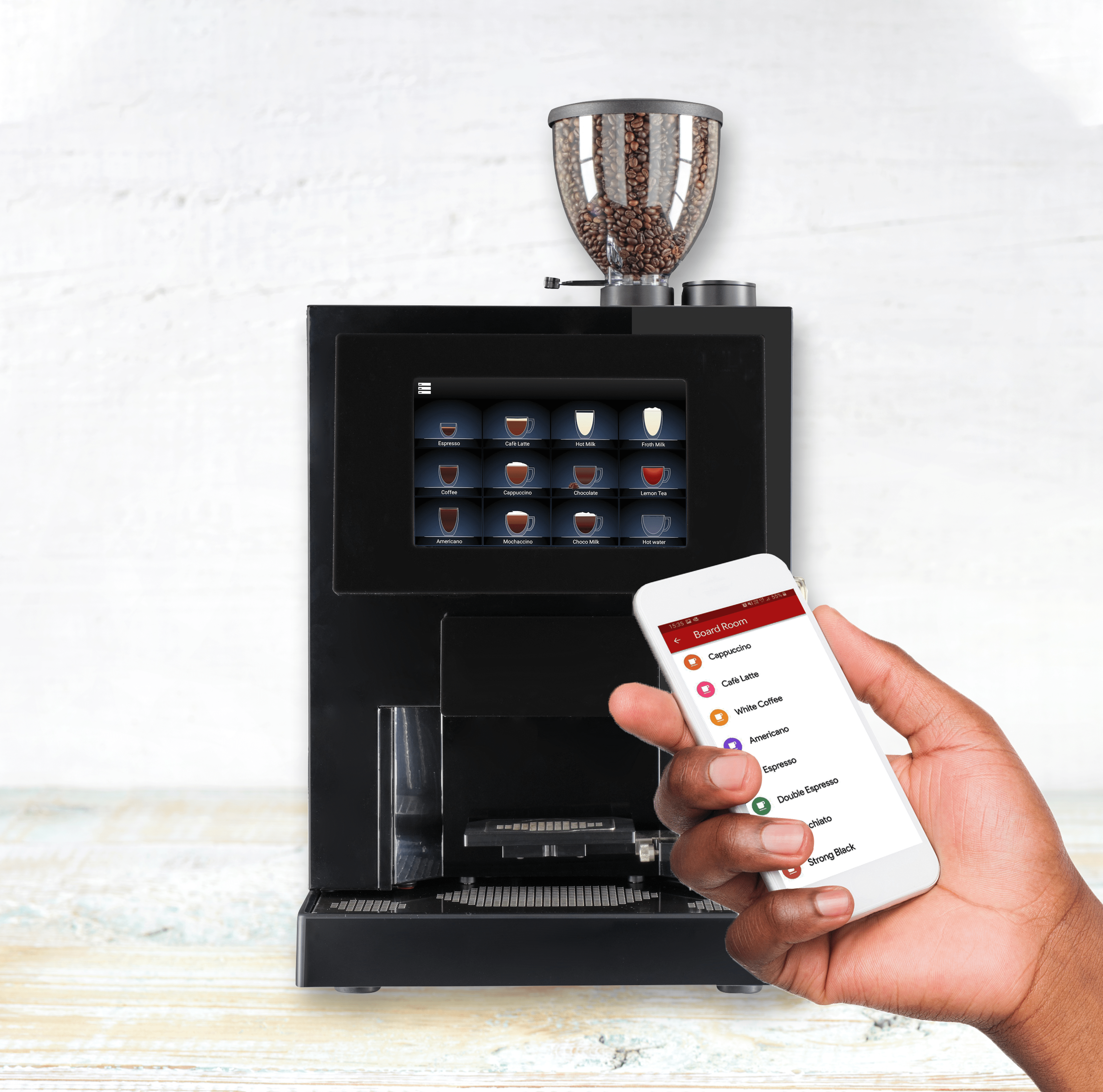 front on photograph of a Cafetouch 8 coffee machine on a white table wood table with full bean hopper and a hand holding a mobile phone position in front of the machine to the bottom right of the image the phone has a cafetouch app on the screen