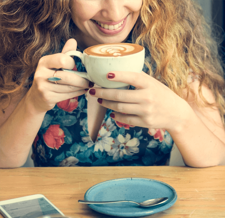 Woman enjoying a cappuccino coffee