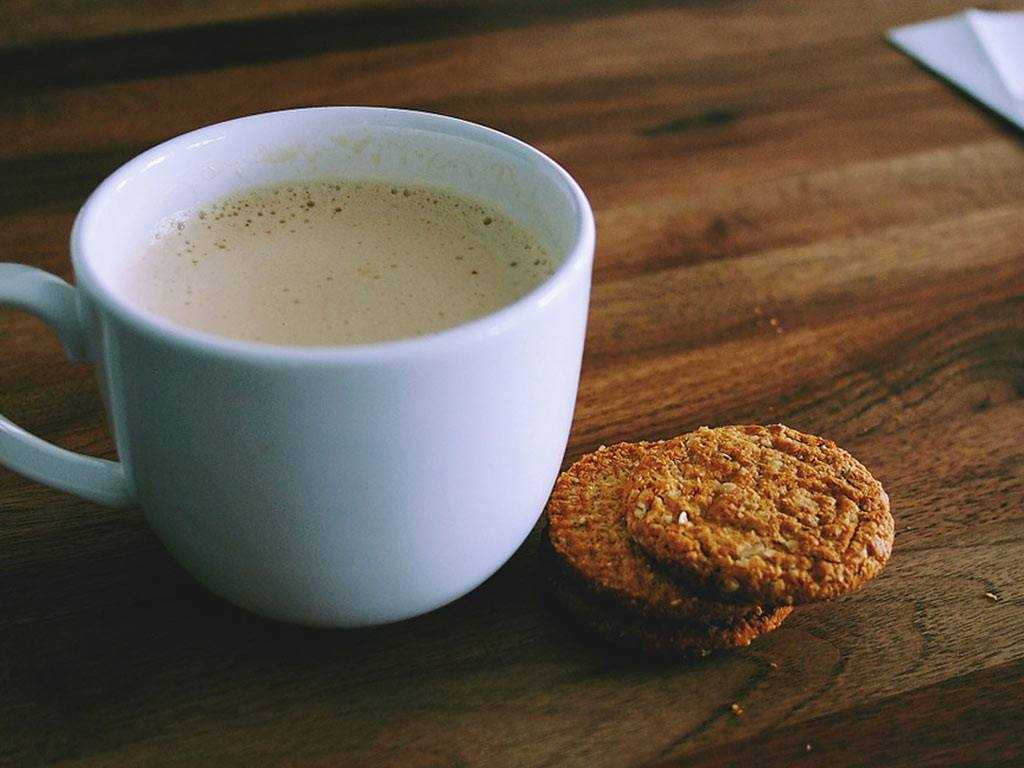 cup of coffee next to oat biscuits