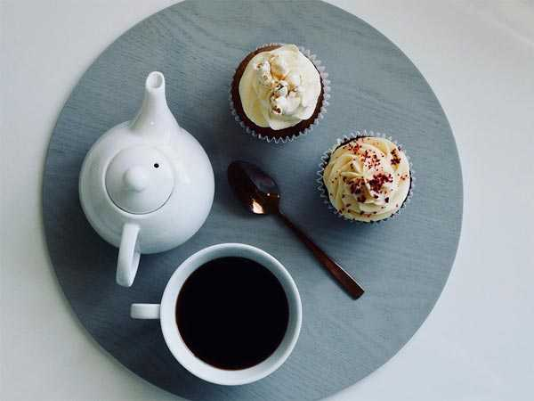 cup of tea next to a spoon and cupcakes
