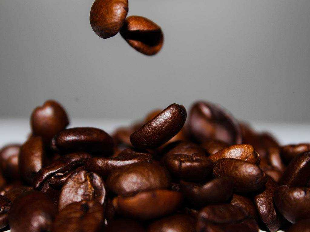 dark roasted coffee beans falling