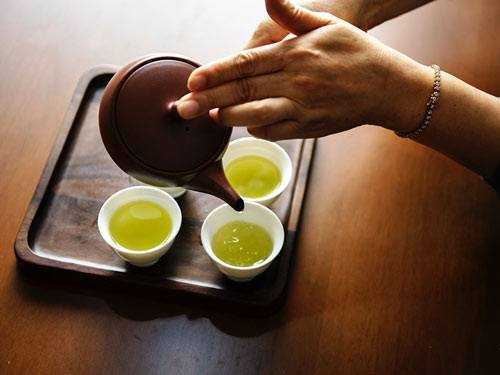 woman pouring green tea into cups