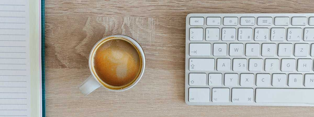 coffee by a computer keyboard