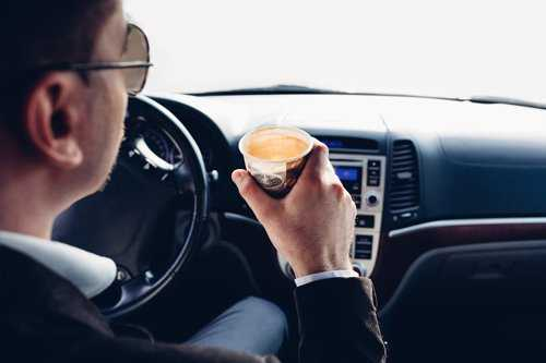 man driving with coffee in hand