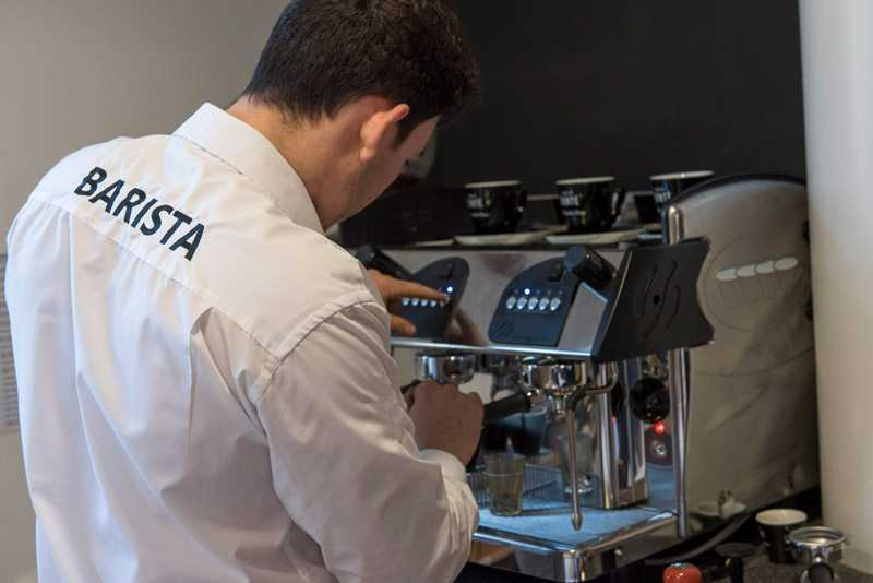 barista using traditional espresso machine