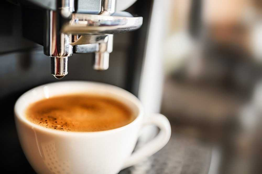 Commercial coffee machine dispensing an espresso