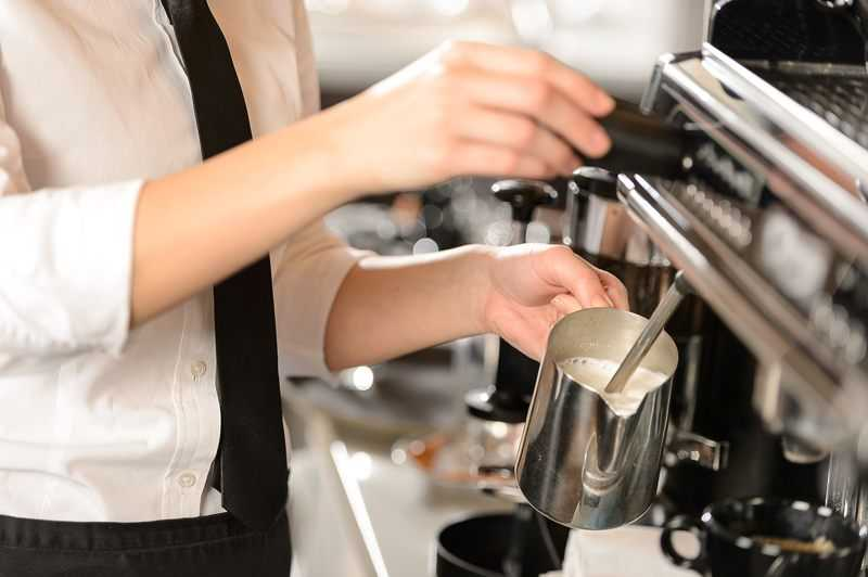 barista frothing milk using a steam wand on traditional espresso machine