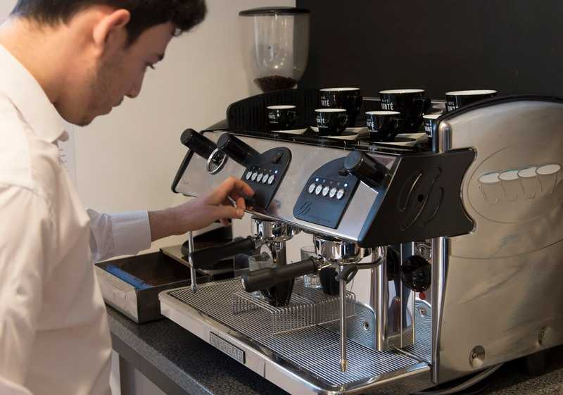 barista using a traditional espresso coffee machine