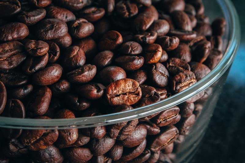dark brown coffee beans in a bowl