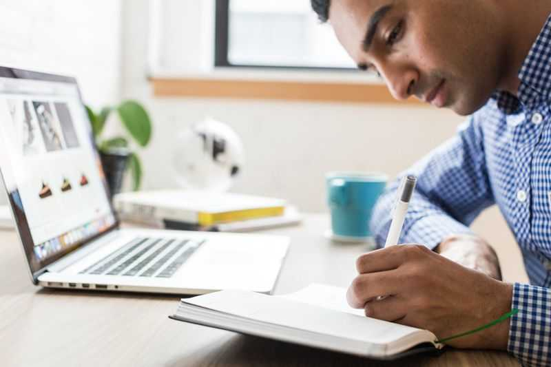 man working alone with laptop and notebook