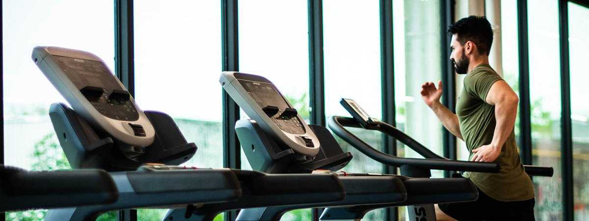 man running on treadmill in a gym