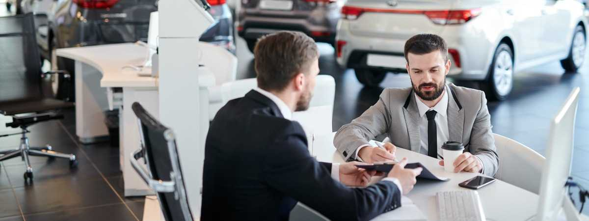 Two people doing paperwork in a car dealership