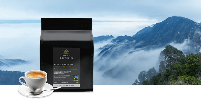 PICCO COFFEE CO FAIRTRADE MISTY MOUNTAIN COFFEE BEANS AGAINST A BACKGROUND OF MOUNTAINS