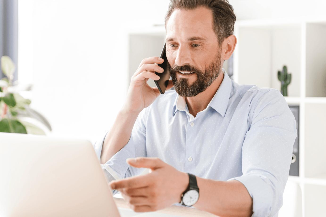man looking at laptop talking on phone