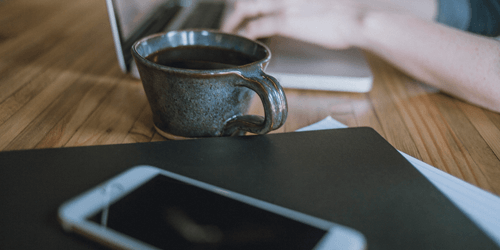 Person working on laptop with cup of coffee and smartphone near by