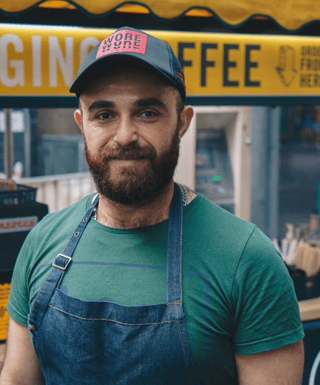 Barista standing next to Change Please coffee cart