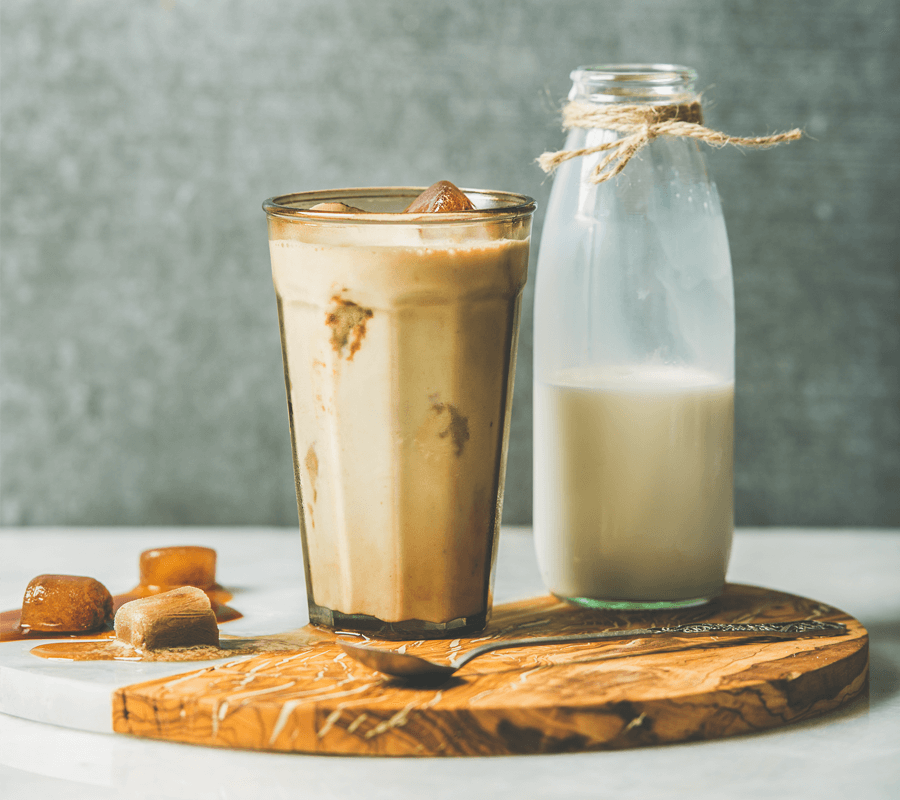 Iced latte next to a bottle of milk and some ice cubes